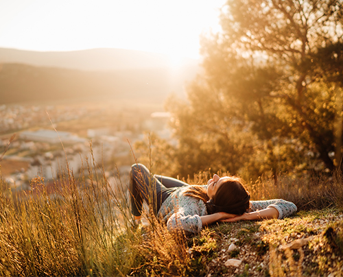 woman relaxing on golden hilltop
